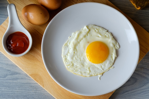 L'œuf au plat est dans un plat rond blanc placé sur une planche à découper concept alimentaire