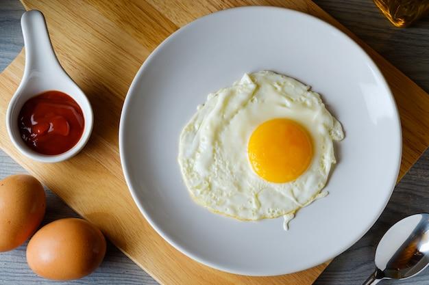 L'œuf au plat est dans un plat rond blanc placé sur une planche à découper, vue de dessus concept alimentaire