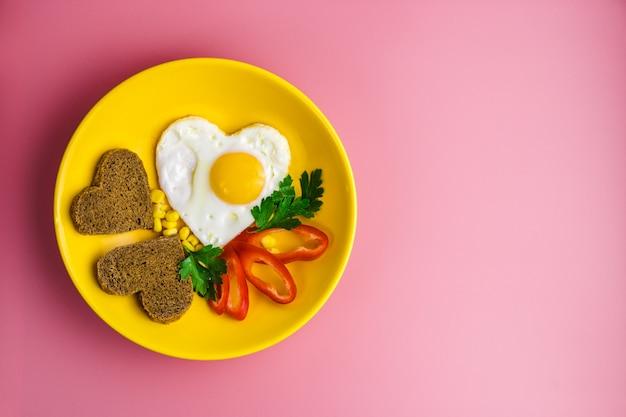 Oeuf au plat en forme de coeur et pain dans une assiette jaune sur fond rouge. la saint-valentin