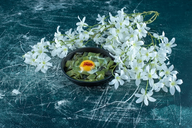 Oeuf au plat avec des haricots verts dans une casserole. photo de haute qualité