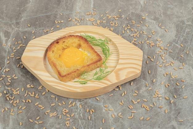 Oeuf au plat à l'intérieur d'une tranche de pain grillé sur une plaque en bois. photo de haute qualité