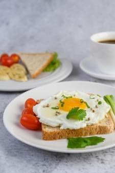 Un œuf au plat portant sur un toast, garni de graines de poivre avec des carottes et des oignons de printemps.