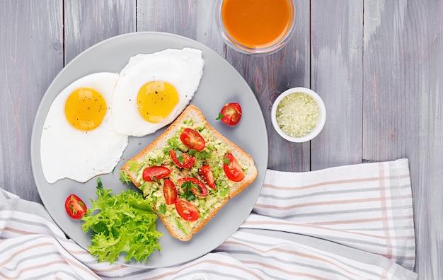 Oeuf au plat, salade de légumes et sandwich à l'avocat grillé