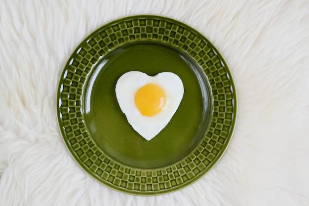 Oeuf au plat savoureux en forme de coeur servi sur une plaque verte