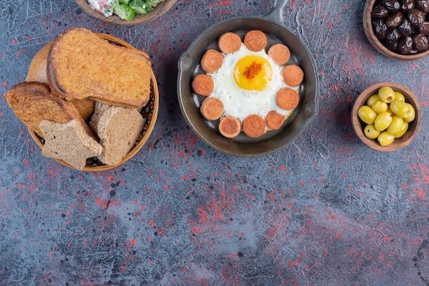 Oeuf au plat servi avec des saucisses grillées et des épices sur un plateau en bois.