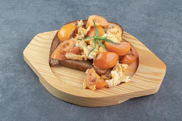 Oeuf au plat, tomates et pain sur plaque de bois.