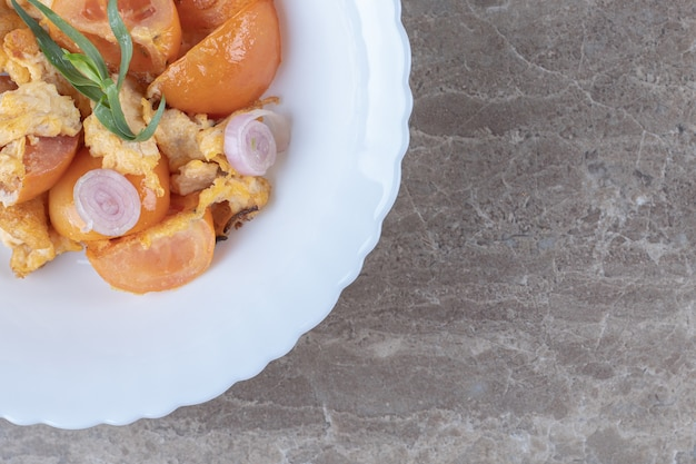 Oeuf au plat et tomates sur plaque blanche.