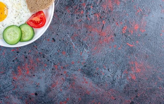 Oeuf au plat avec des tranches de concombre, de tomate et de pain.