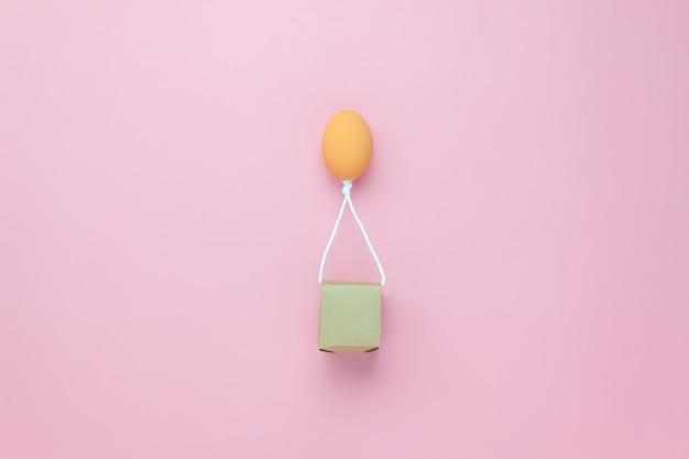 Oeuf ballon battant transfert boîte-cadeau sur papier rose ciel avec des nuages au bureau.