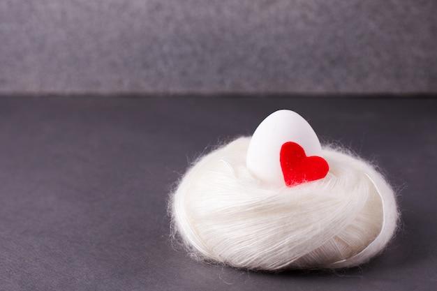 Un oeuf blanc avec un coeur rouge se trouve dans un nid douillet chaud et confortable