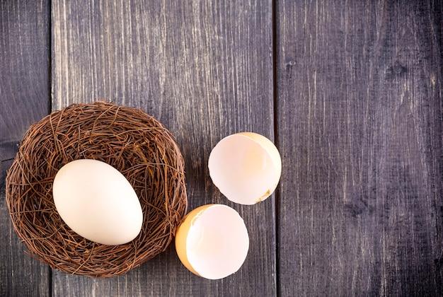 L'œuf blanc sur le nid sur le vieux fond en bois