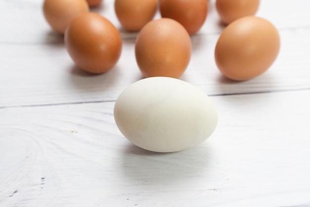 Œuf blanc avec plusieurs œufs sur du bois blanc