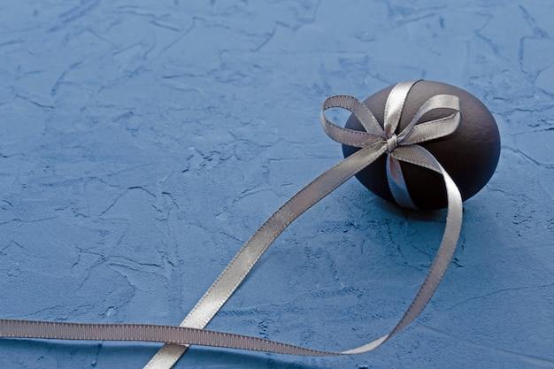 Oeuf bleu avec un ruban de satin gris sur un bleu classique