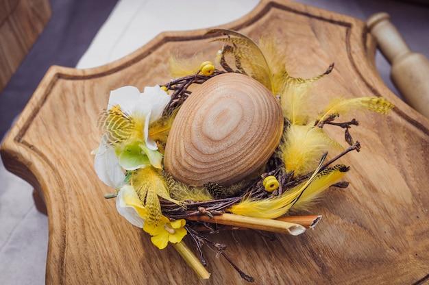 Oeuf en bois dans une couronne de plumes, fond de vacances de pâques