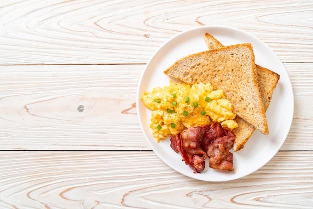 Oeuf brouillé avec pain grillé et bacon pour le petit déjeuner