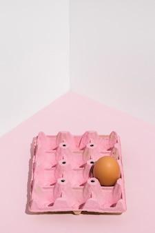 Œuf brun dans une grille rose sur une table lumineuse