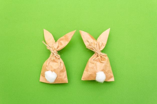 Oeuf de cadeau de lapin de pâques papier emballage idée de bricolage sur fond coloré. concept de pâques minimal, pose à plat, gros plan.