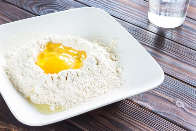 Oeuf cassé dans la farine dans une assiette blanche, cuillère sur assiette. les rayons du soleil sur la table.