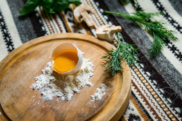 Oeuf cassé dans la farine sur une planche à découper ronde, sur une table en bois foncé avec serviette