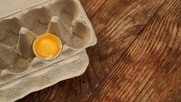Un œuf cassé dans un plateau à œufs en carton. demi oeuf avec du jaune dans une boîte vide sur fond de bois