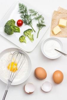 Oeuf cassé avec de la farine dans un bol. fouetter sur un bol. beurre sur papier. brocoli, tomates et aneth en assiette. mise à plat