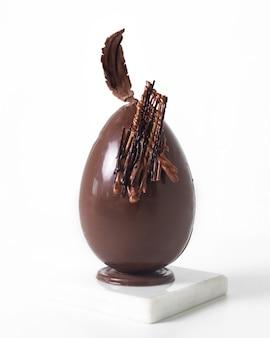 Oeuf en chocolat vue de face sur le sol blanc