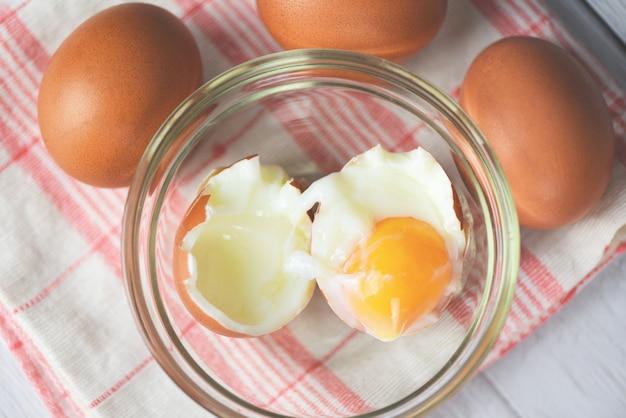 Œuf à la coque sur un bol en verre et œufs frais sur la table