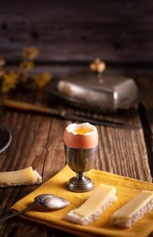 Œuf à la coque dans un coquetier en argent avec du pain et du fromage sur une table en bois