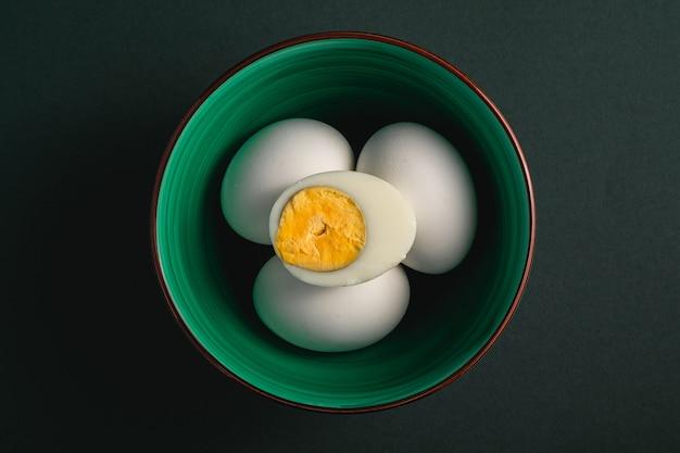 Œuf à la coque avec du jaune d'oeuf avec des œufs blancs dans un bol vert sur fond noir
