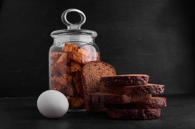 Oeuf, craquelins et tranches de pain sur la table.