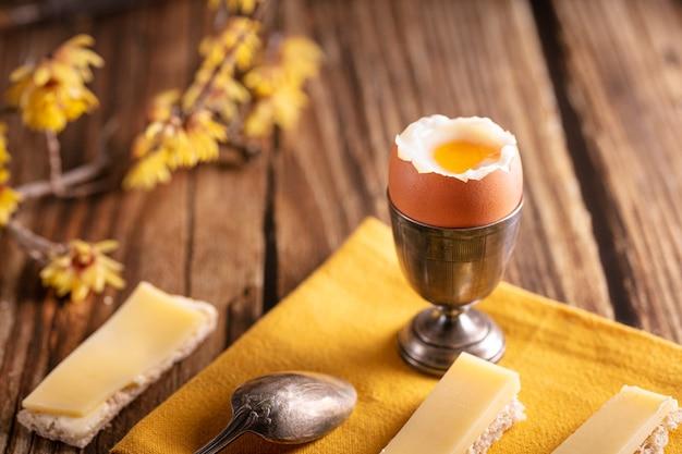 Œuf dur dans un coquetier en argent avec du pain et du fromage sur une table en bois