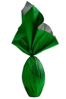 Oeuf de l'est brésilien enveloppé dans du papier vert sur un mur blanc