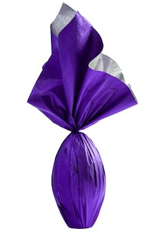 Oeuf de l'est brésilien enveloppé dans du papier violet sur un mur blanc