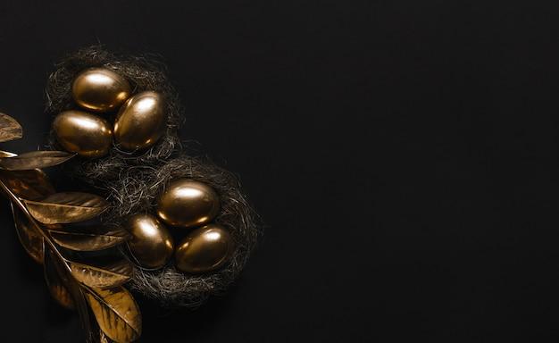 L'œuf est peint en or dans un nid de paille et la plante aux feuilles d'or sur un tableau noir