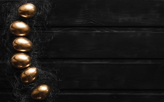 L'œuf est peint en or dans un panier sur une table en bois noir avec vue de dessus