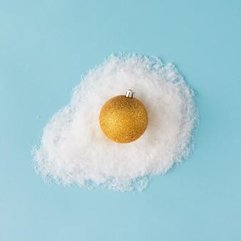 Oeuf fait de décoration de boule de noël dorée et de neige. mise à plat. concept de noël.