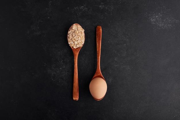 Oeuf et farine sur des cuillères en bois dans un style croisé.