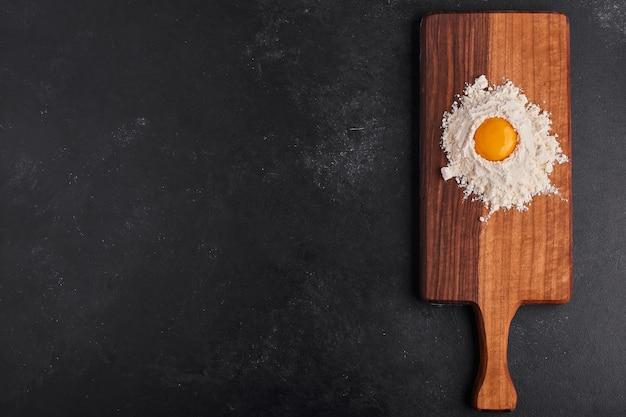 Oeuf et farine mélangés les uns aux autres sur une planche de bois sur une surface noire.