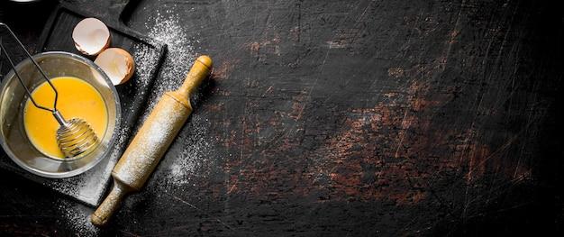 Œuf avec fouet et rouleau à pâtisserie.