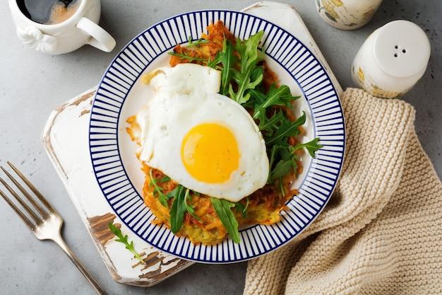 Œuf frit avec crêpe de pommes de terre, roquette et avocat sur une plaque en céramique pour le petit déjeuner. vue de dessus.