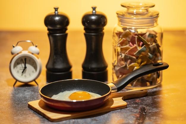 Œuf frit dans une casserole debout sur la table de cuisine à côté du réveil