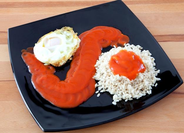 Œuf frit avec du riz trop cuit et de la tomate