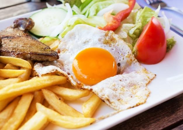 Œuf frit avec frites de pommes de terre, steak grillé et légumes.