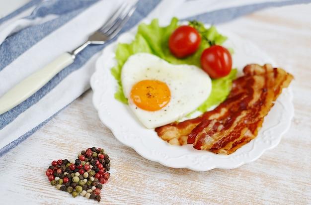 Oeuf frit savoureux en forme de coeur servi sur une plaque blanche avec bacon tomate salade feuilles poivre fond en bois saint valentin matin
