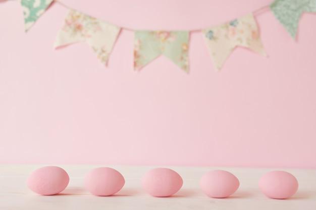 Oeuf et guirlande peints en rose de pâques