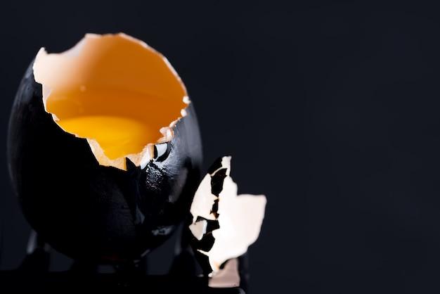 Oeuf noir avec jaune et gouttes sur le bord d'une coquille noire
