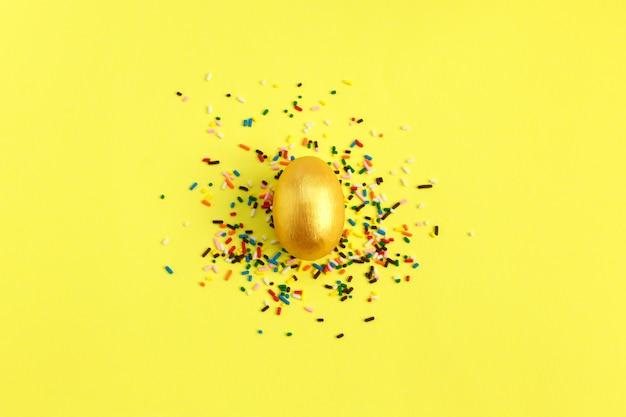 Oeuf d'or avec des bonbons colorés pépite sur fond jaune.