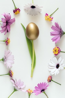 Oeuf d'or comme une fleur de tulipe avec des fleurs colorées sur fond blanc
