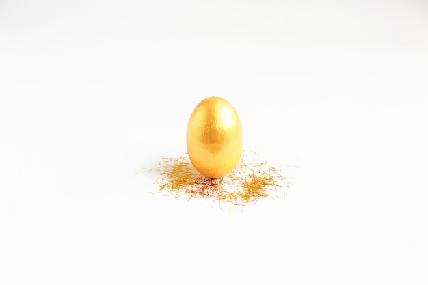 Œuf d'or, symbole de l'argent et des investissements réussis, debout sur un fond blanc.