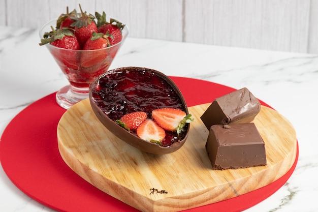 Oeuf de pâques au chocolat farci de confiture de fraises à côté de blocs et de pépites de chocolat et d'un bol de fraises. paysage de pâques.